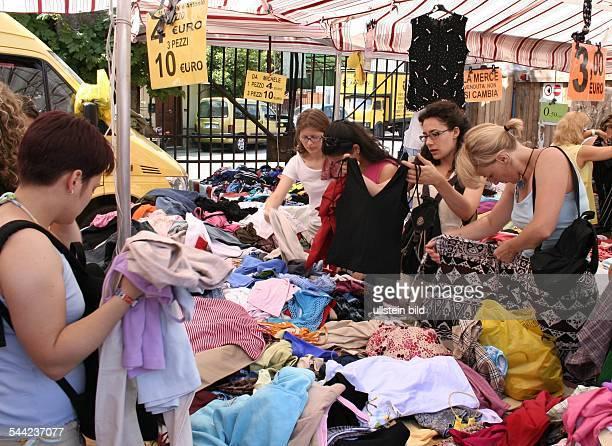 Italien, Rom - Kunden auf dem Porta Portese Markt. Wuehltisch mit Textilien und Sonderangeboten.