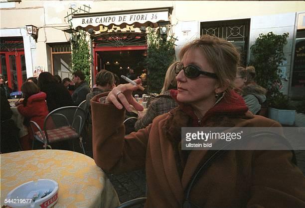 Italien Rom Rauchverbot in allen Gebauden Cafes und Restaurants vietato fumare Raucherin raucht im Freien vor einem Restaurant eine Zigarette