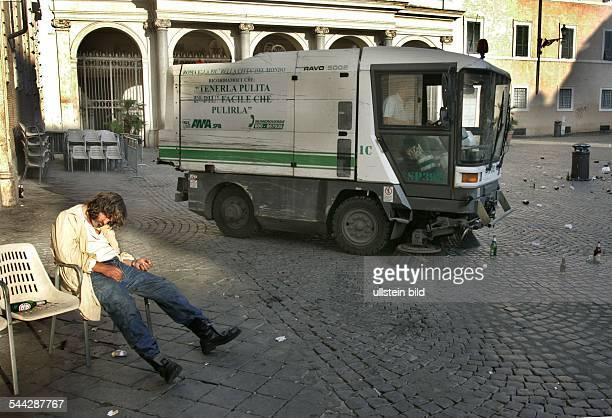 Italien Rom Trastevere Kehrmaschine reinigt die Piazza S Maria ein Obdachloser schlaeft im Stuhl eines Restaurants
