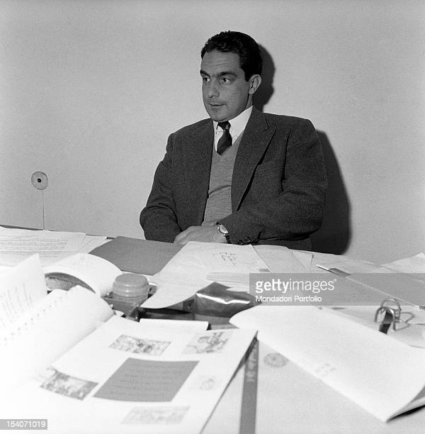 Italo Calvino italian writer and Einaudi publishing company's associate sits at his desk filled with paperwork Turin July 1959