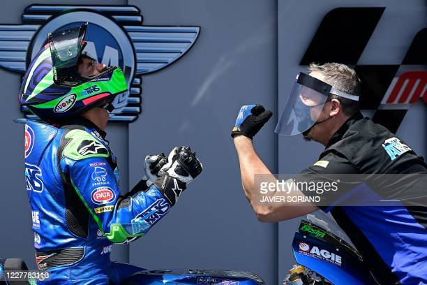 Italtrans Racing Team's Italian rider Enea Bastianini celebrates with a team member after winning the Moto2 race during the Andalucia Grand Prix at...