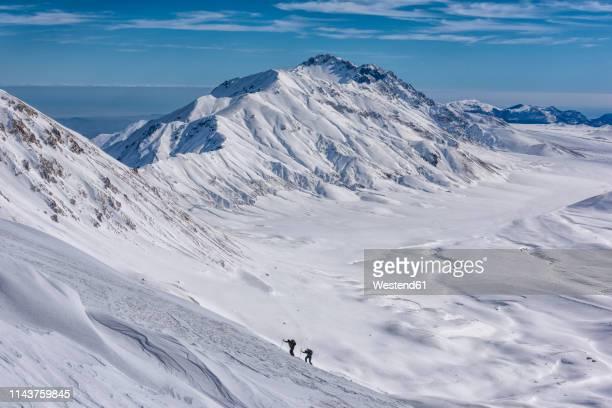 italy, abruzzo, gran sasso e monti della laga, hikers on campo imperatore plateau in winter - カンポ・インペラトーレ ストックフォトと画像