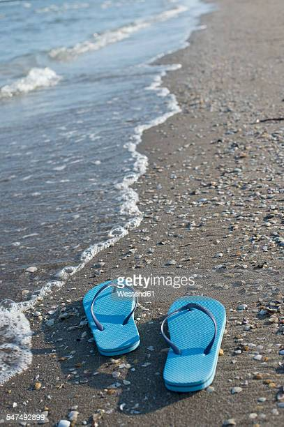 italy, adriatic sea, blue flip-flops at seafront - sandal stock pictures, royalty-free photos & images