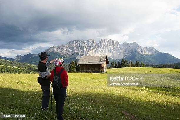 Italy, Alto Adige, Dolomites, Latemar, couple in meadow, rear view