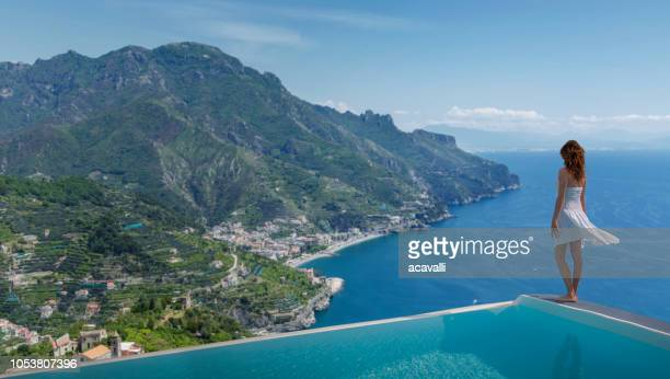 italy. amalfi coast. woman in infinity pool. - campania stock pictures, royalty-free photos & images