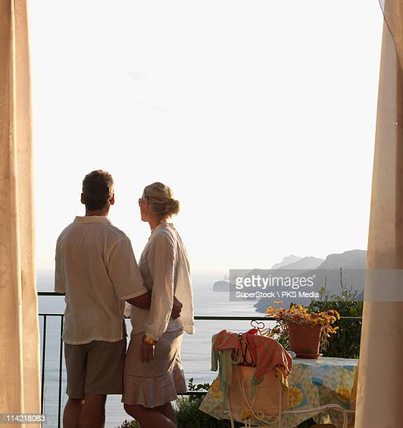 Italy, Amalfi, Couple look out from hotel suite over positano