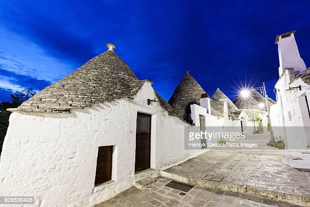 italy, apulia, alberobello, trulli houses along illuminated street under blue sky - alberobello stock photos and pictures