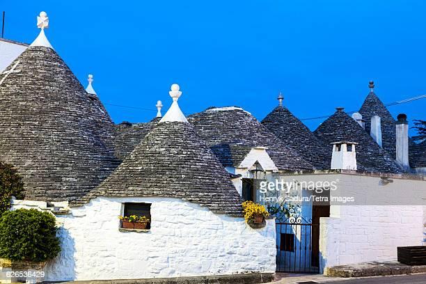 italy, apulia, alberobello, trulli houses under blue sky - alberobello stock photos and pictures