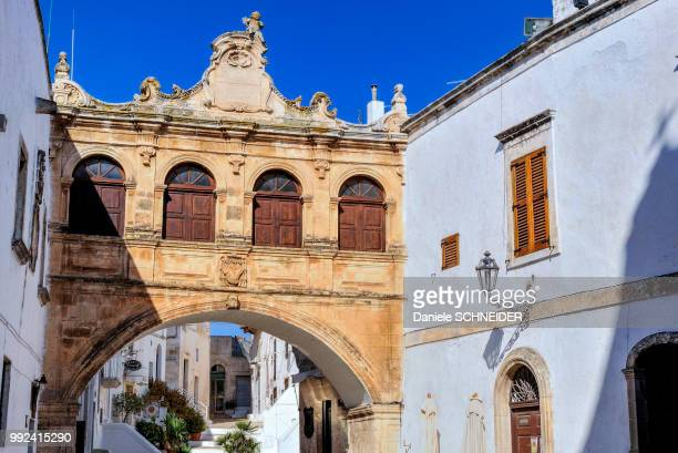 italy, apulia, itria valley, ostuni, scoppa arch of the seminary - ostuni stock photos and pictures