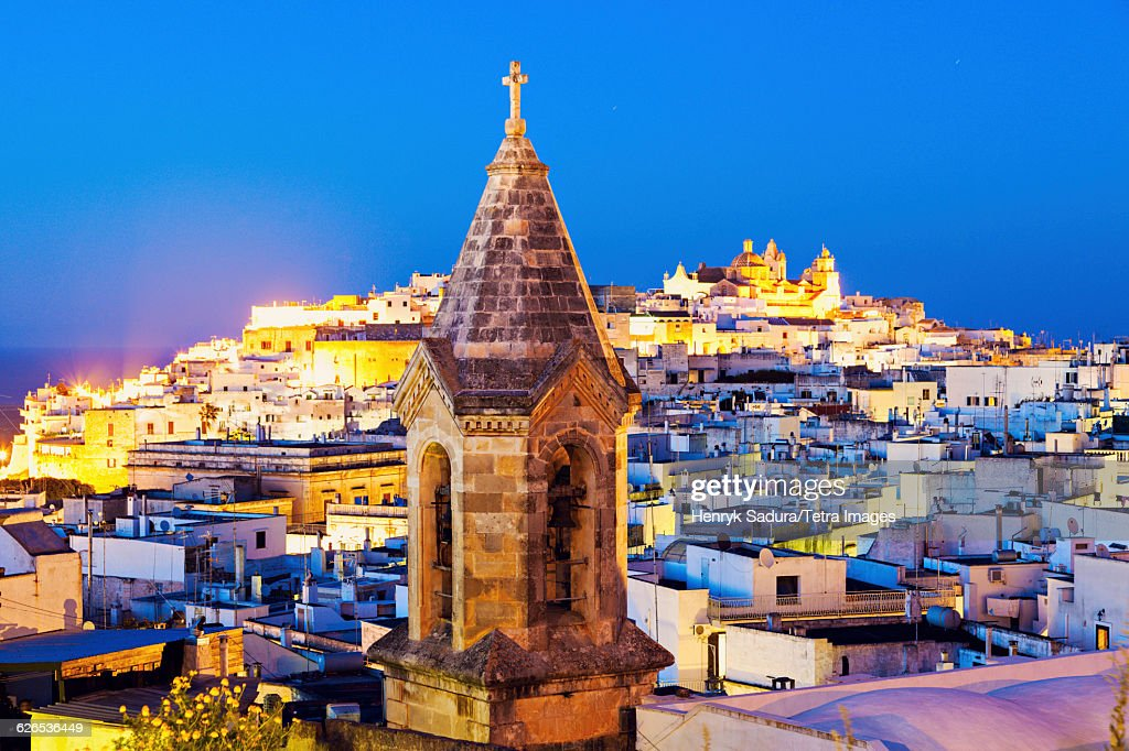 Italy, Apulia, Ostuni, Illuminated townscape with church tower in foreground at dusk : Stock Photo