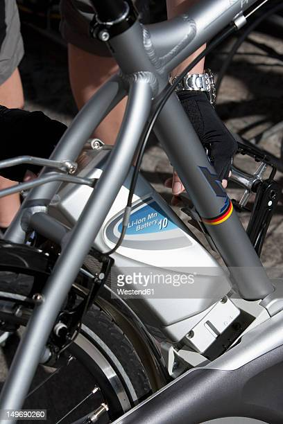 Italy, Arco,  Mid adult woman with electric bicycle