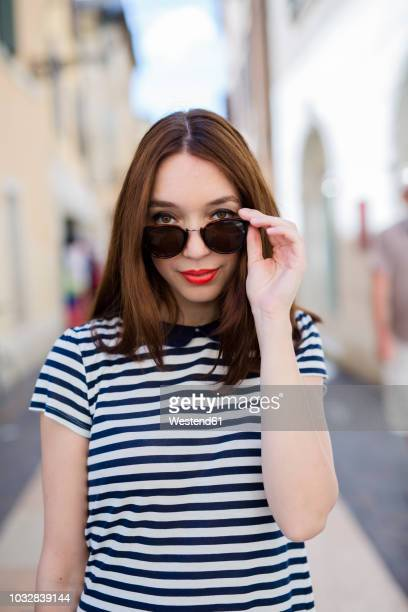 Italy, Bardolino, portrait of young woman with red lips and sunglasses