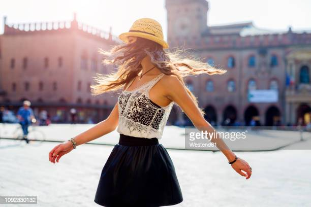 italy, bologna, young woman dancing on square - jupe vent photos et images de collection