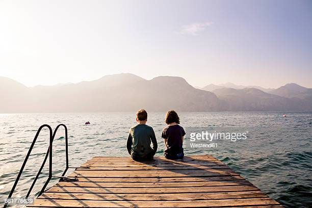 Italy, Brenzone, back view brother and sister sitting side by side on jetty