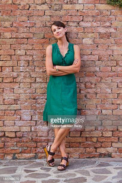 italy, burano, portrait of mature woman leaning against brick wall - green dress stock pictures, royalty-free photos & images