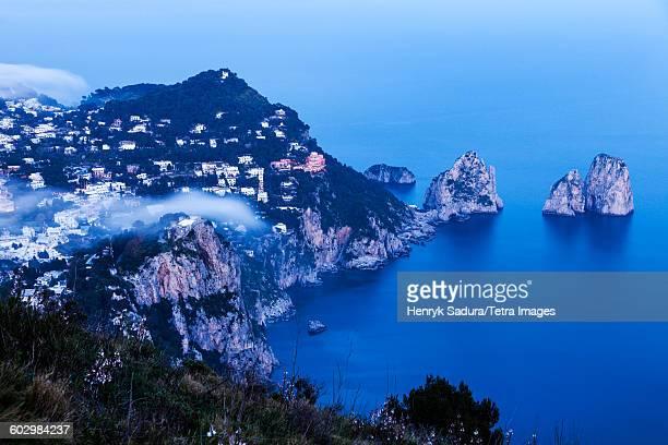 Italy, Campania, Capri Island, Capri, Coastal town and Faraglioni at sunset