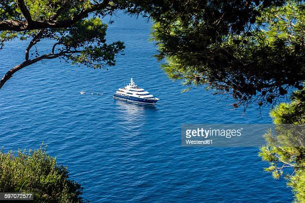 italy, capri, luxury yacht anchoring at steep coast - yacht de luxe photos et images de collection
