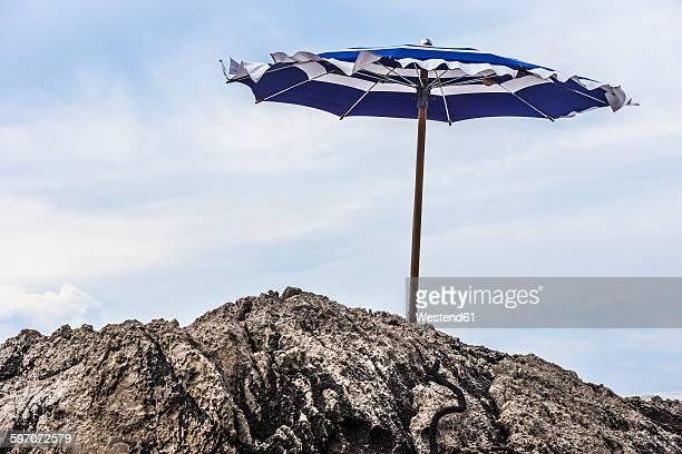italy, capri, sunshade at rocky coast - costa rocciosa foto e immagini stock