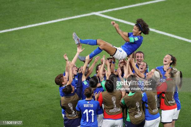Italy celebrate progressing to the knockout stages by throwing captain Sara Gama into the air during the 2019 FIFA Women's World Cup France group C...