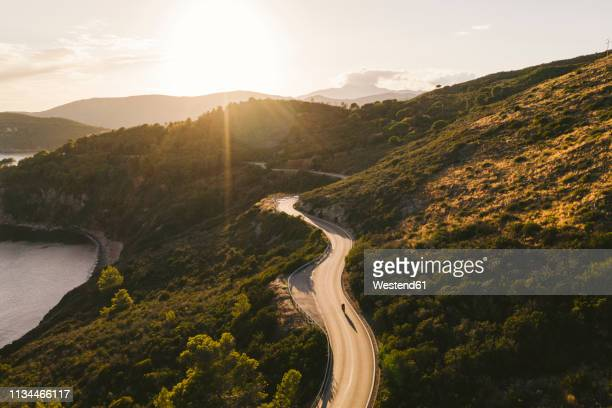 italy, elba island, biker on coastal road against the sun, aerial view with drone - motorcycle stock pictures, royalty-free photos & images