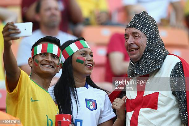 Italy fans pose for a photograph with an England fan ahead of the 2014 FIFA World Cup Brazil Group D match between England and Italy at Arena...