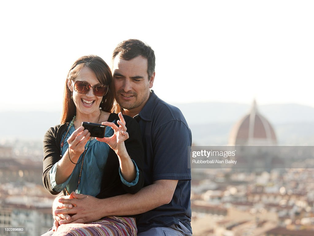 Italy, Florence, Couple viewing camera at lookout over old town : Stock Photo
