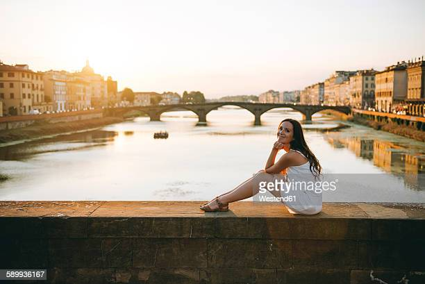 Italy, Florence, happy woman sitting on a bridge at sunset