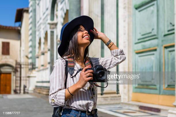 italy, florence, happy young tourist with camera looking up - turista foto e immagini stock