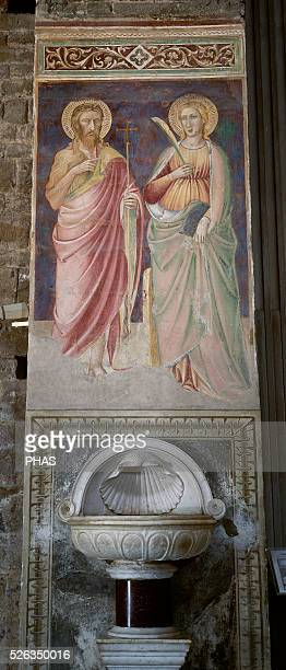 Italy. Florence. Mural painting with saints and holy water font. 14th-15th century. Basilica of San Miniato al Monte.