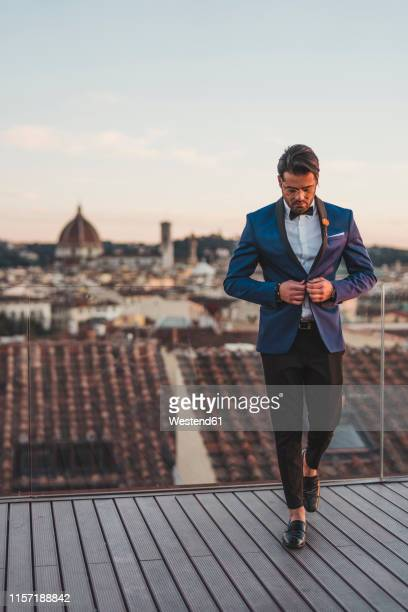 italy, florence, stylish man on roof terrace at sunset - florence italy foto e immagini stock