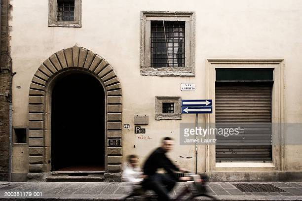 Italy, Florence, two boys cycling past house (blurred motion)