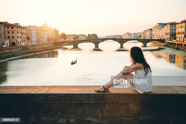 Italy, Florence, woman wearing white summer dress sitting on a bridge at sunset