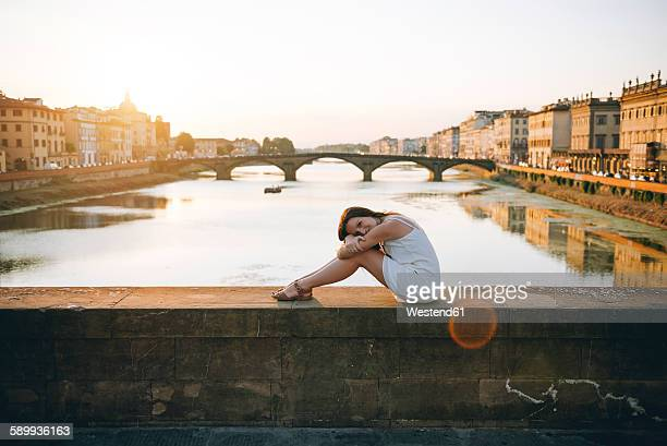Italy, Florence, woman wearing white summer dress sitting on a bridge enjoying the sunset