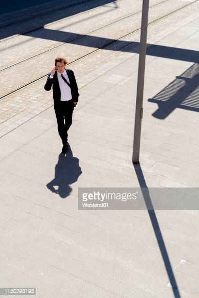 italy, florence, young businessman on smartphone in the city - hands in pockets stock pictures, royalty-free photos & images