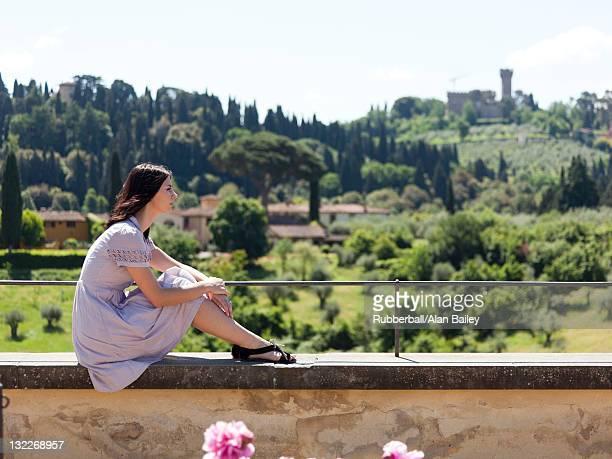Italien, Florenz, junge Frau entspannend auf Wand