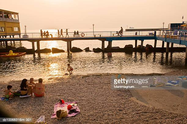 Italy, Friuli Venezia Giulia, Trieste, people at Bagno Ausonia at sunset