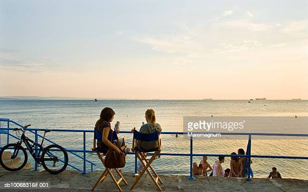 Italy, Friuli Venezia Giulia, Trieste, people at Barcola beach promenade at sunset