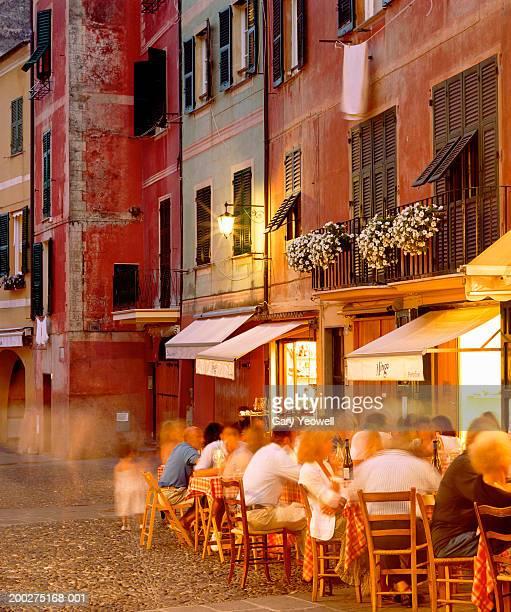 italy, genoa, portofino, diners outside restaurant (long exposure) - portofino stock pictures, royalty-free photos & images
