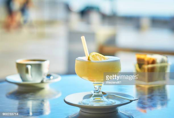 Italy, glass of lemon granita and cup of Cappuccino in the background