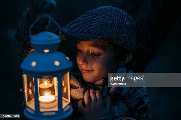Italy, Grosseto, happy boy looking at lighted Christmas lantern by night