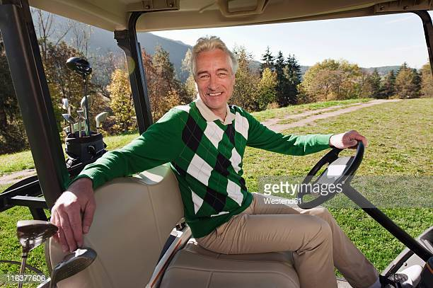 Italy, Kastelruth, Mature man sitting in golf cart on golf course, smiling, portrait