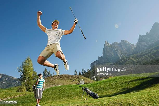 Italy, Kastelruth, Mid adult couple on golf course