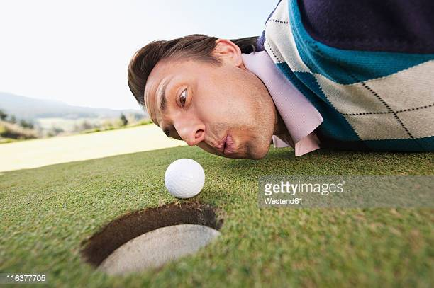 italy, kastelruth, mid adult man blowing golf ball into hole - golf humour photos et images de collection
