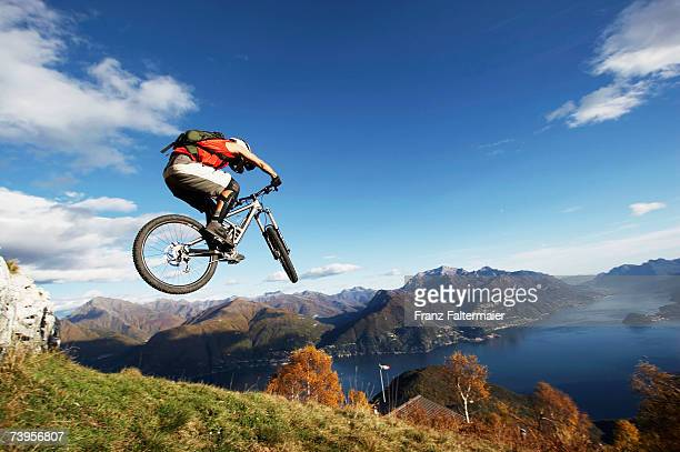 italy, lake como, man performing jump on bicycle - mountain bike stock pictures, royalty-free photos & images