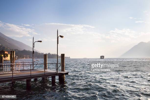 Italy, Lake Garda, Malcesine, Harbor with ferry boat at sunset