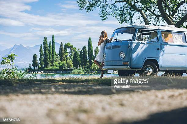 italy, lake garda, young woman drinking coffee at camping bus - landfahrzeug stock-fotos und bilder