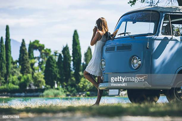 Italy, Lake Garda, young woman drinking coffee at camping bus