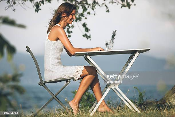 Italy, Lake Garda, young woman sitting at table with laptop