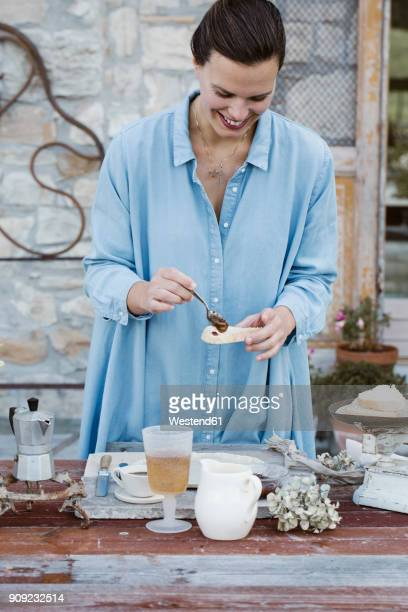 Italy, laughing woman putting jam on slice of bread on terrace