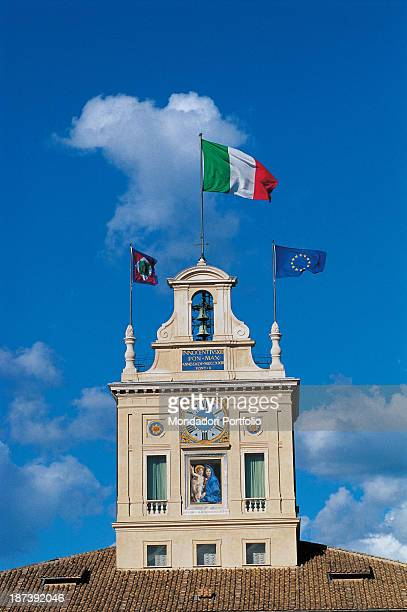 Italy Lazio Rome Palazzo del Quirinale All View of the belltower placed on the roof with flags balconies and loopholes Blue sky in the background